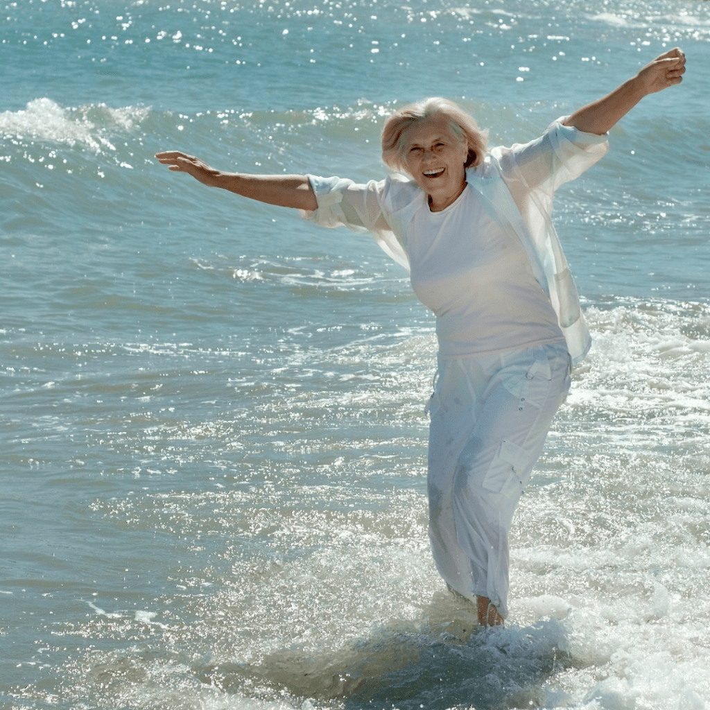happy older woman in white pants and blouse in the ocean with her arms out